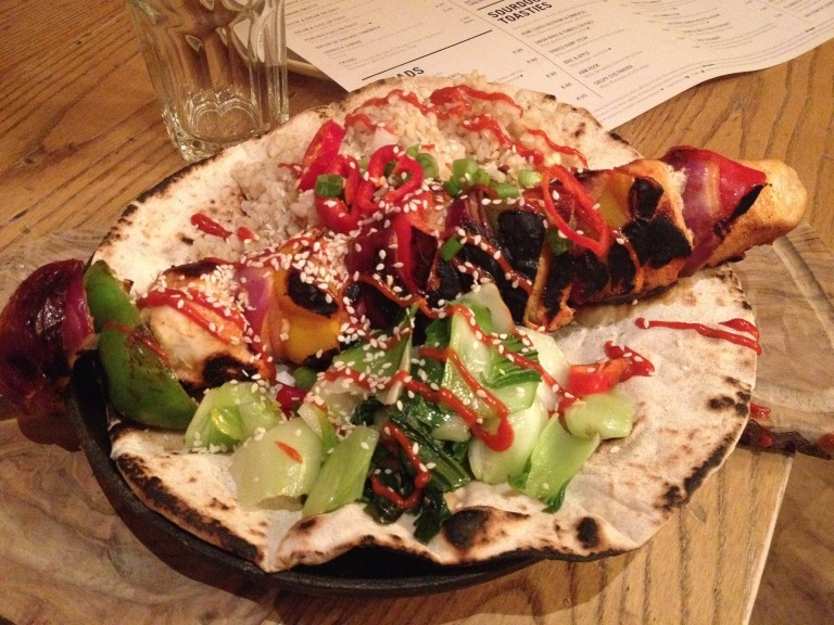 Chicken skewer with brown rice, chillies, sesame seeds, pak choi and gochujang ketchup, on flatbread.